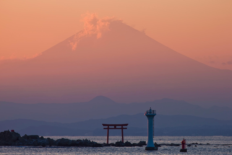 从神奈川县叶山的真名濑海岸望向森户神社。名岛(又名菜岛)上竖立着鲜红的鸟居和叶山灯塔(又名裕次郎灯塔)。