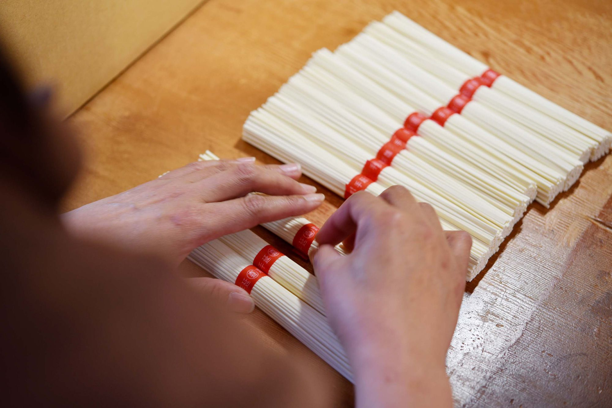 白いそうめんに赤い帯が可愛らしい。手作業で帯を巻いていく。