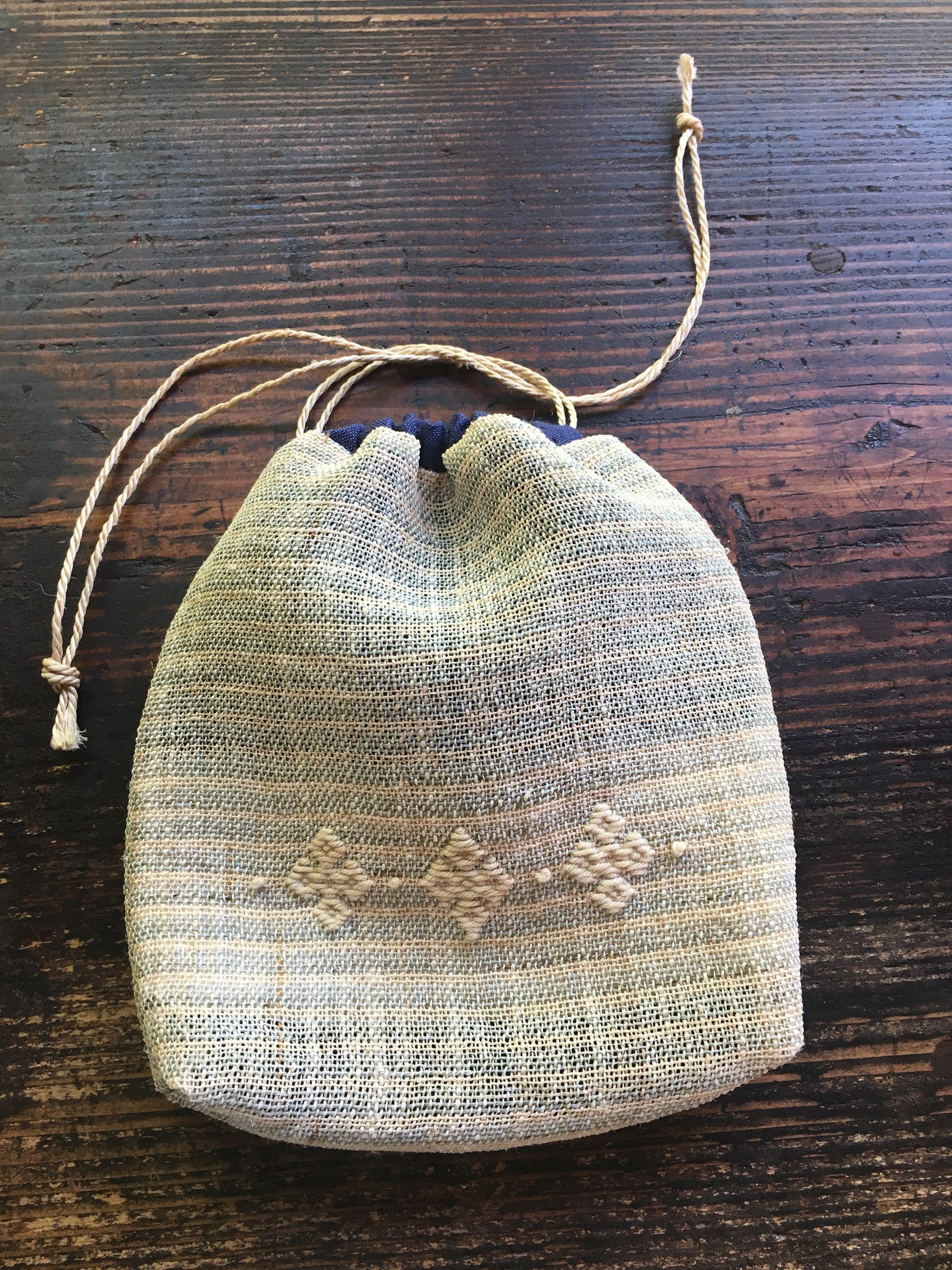 こぎんを刺したからむしの布を会津木綿と合わせた、かわいらしい巾着。Photography by Masako Suda