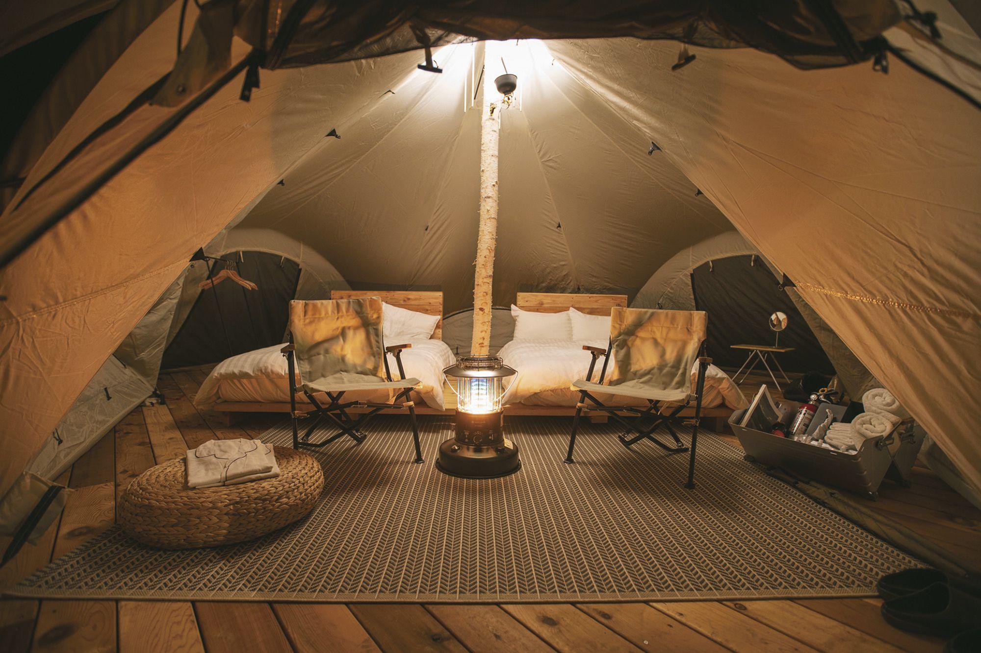 ダブルサイズベッド2台が設置された特別仕様のテント内。ランプの灯りが優しく照らす。