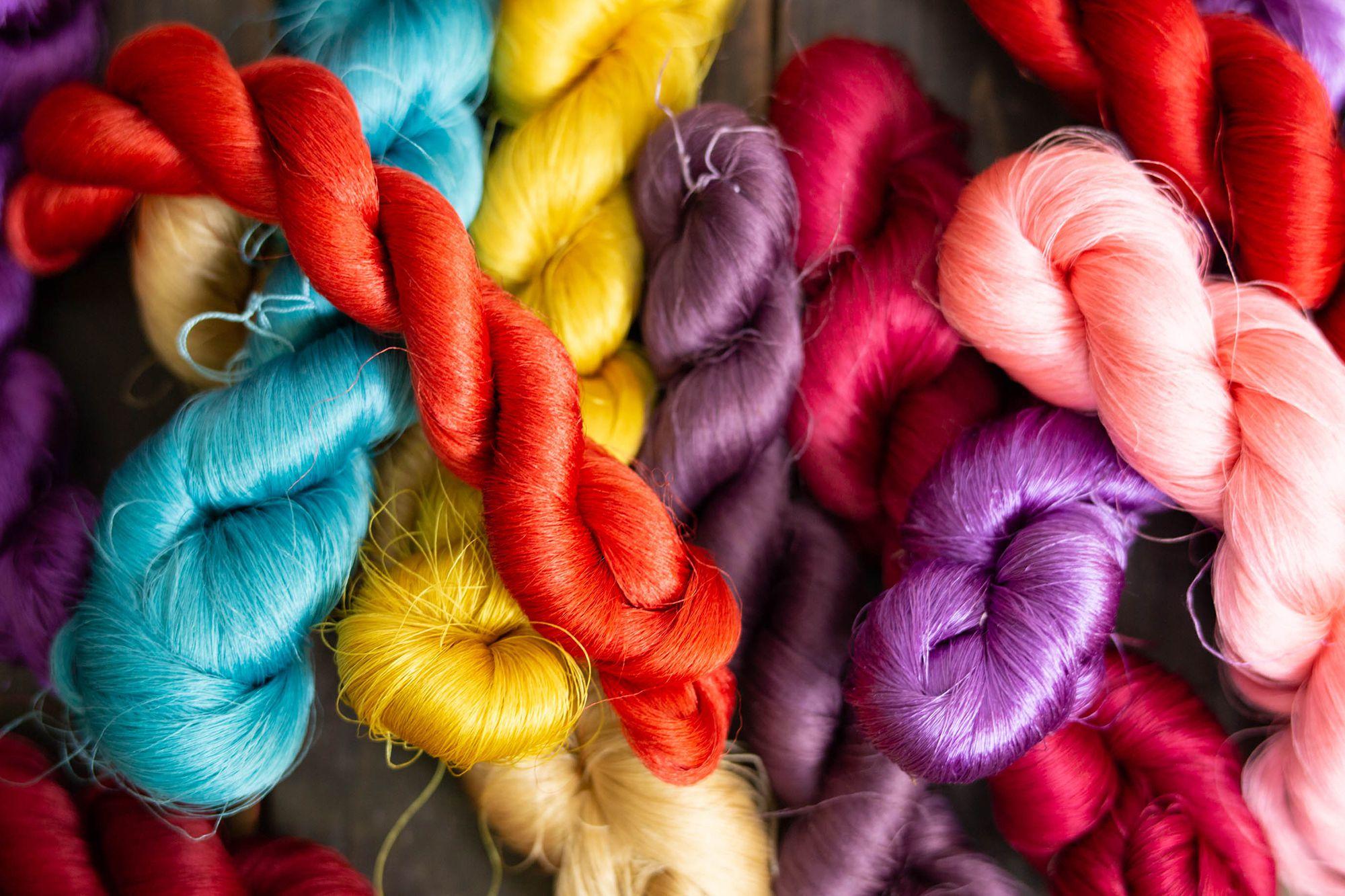 織物用の糸。帯などの織物は、糸を染めて織り上げる。艶やかな絹糸が自然の色合いをまとって輝いている。