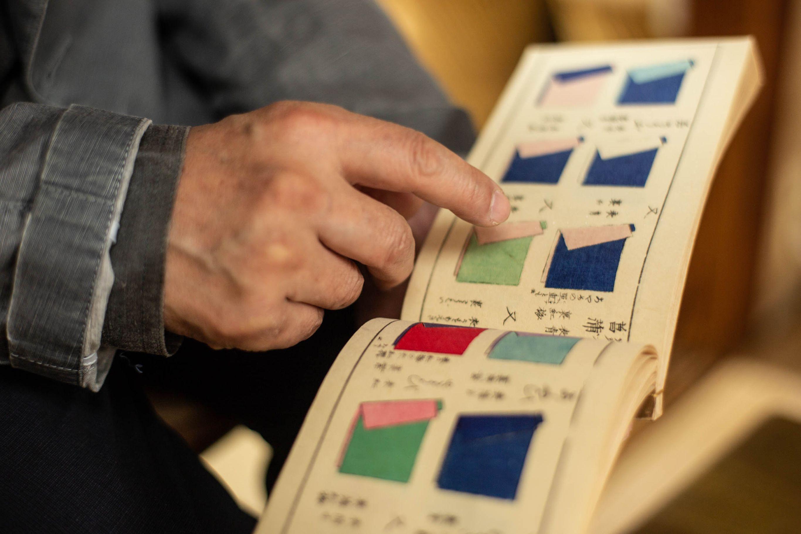『薄様色目』という文政9(1826)年出版の古書を見る吉岡。四季それぞれの襲(かさね)色が木版刷で表されている。この本が襲の色目を再現するきっかけとなった。