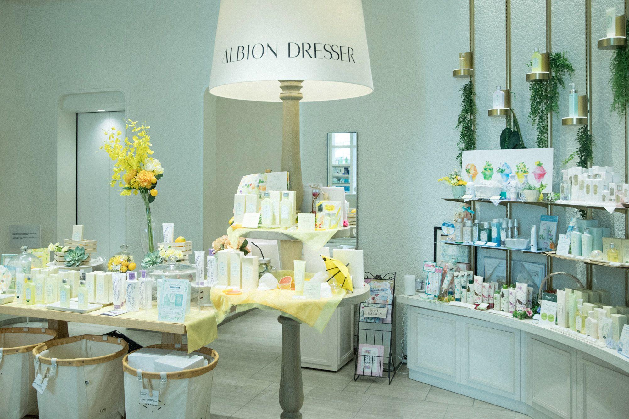 ランプと大きなテーブルが印象的な「アルビオンドレッサー銀座店」。季節に合わせて、おすすめの商品が並ぶ。