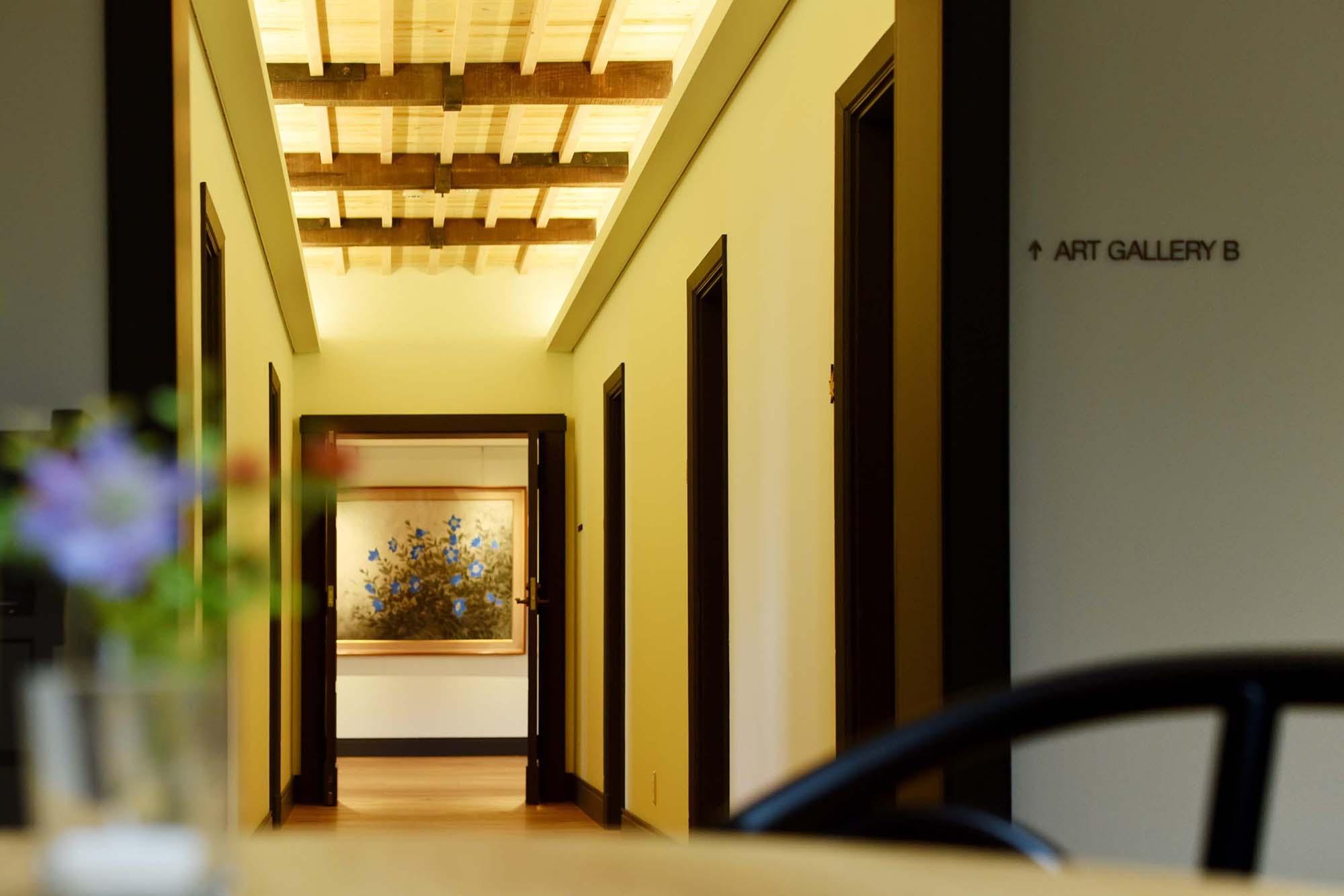 旧館2階はステンドグラスのカフェを中心に、左右にギャラリーエリアと個室エリアを有する。写真奥はギャラリースペース。