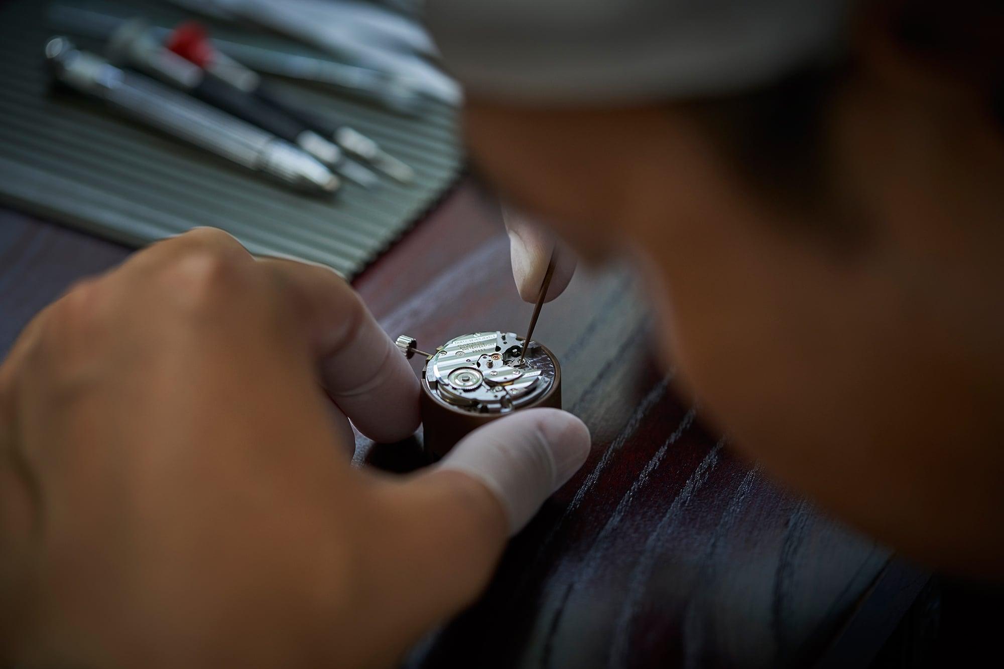 工房内では、極小サイズの部品を顕微鏡をのぞきながら、息をつめて作業を進める。製作しているのはキャリバー9S85。