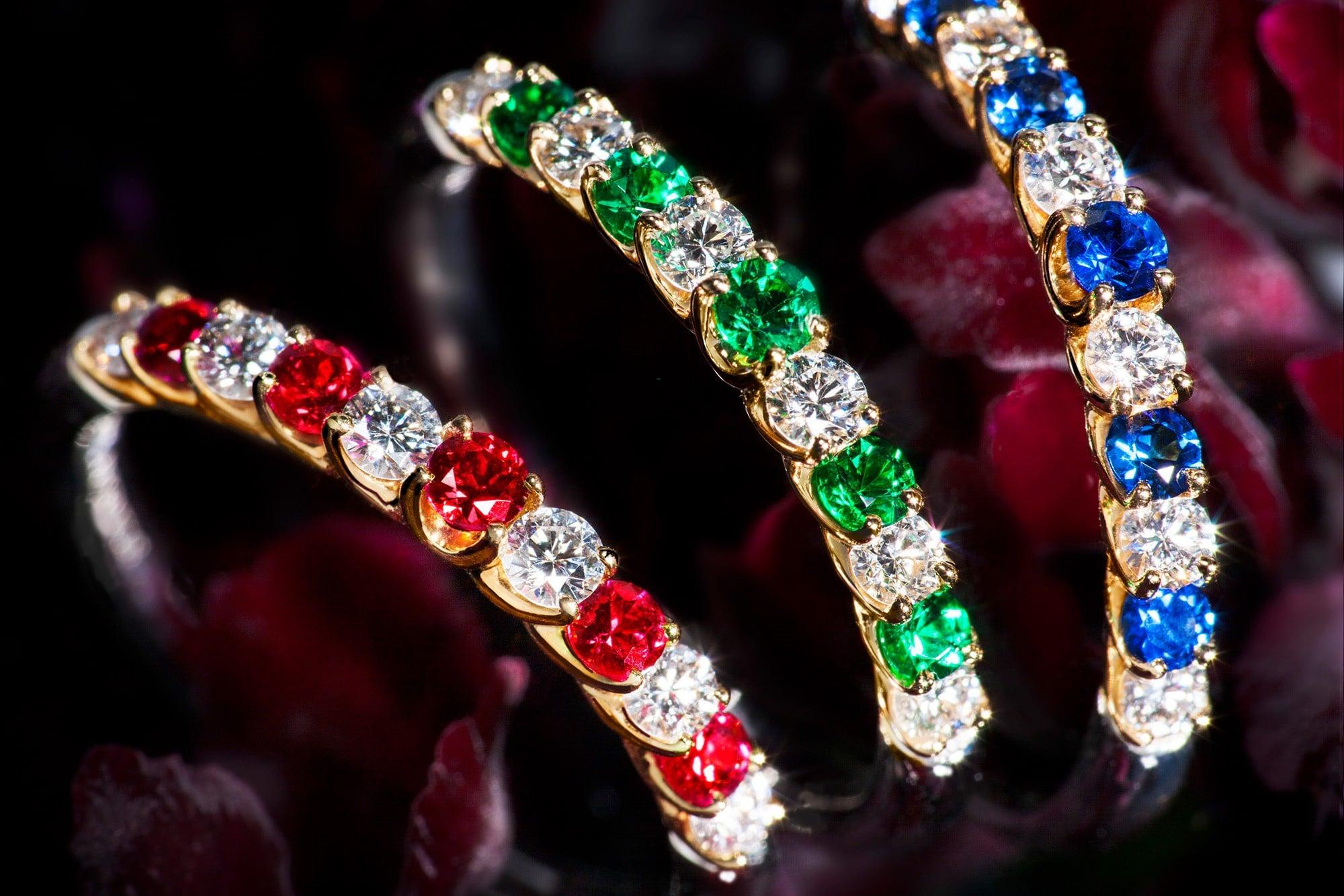 """组合镶嵌了钻石和宝石的婚戒。所采用的钻石、红宝石、蓝宝石、未经加工的祖母绿都由采购员千挑万选,是精品中的精品。 """"纪念 婚戒""""均采用铂金/18K黄金、钻石。从右开始/蓝宝石363,000日元、绿宝石495,000日元、红宝石363,000日元 均为含税价"""