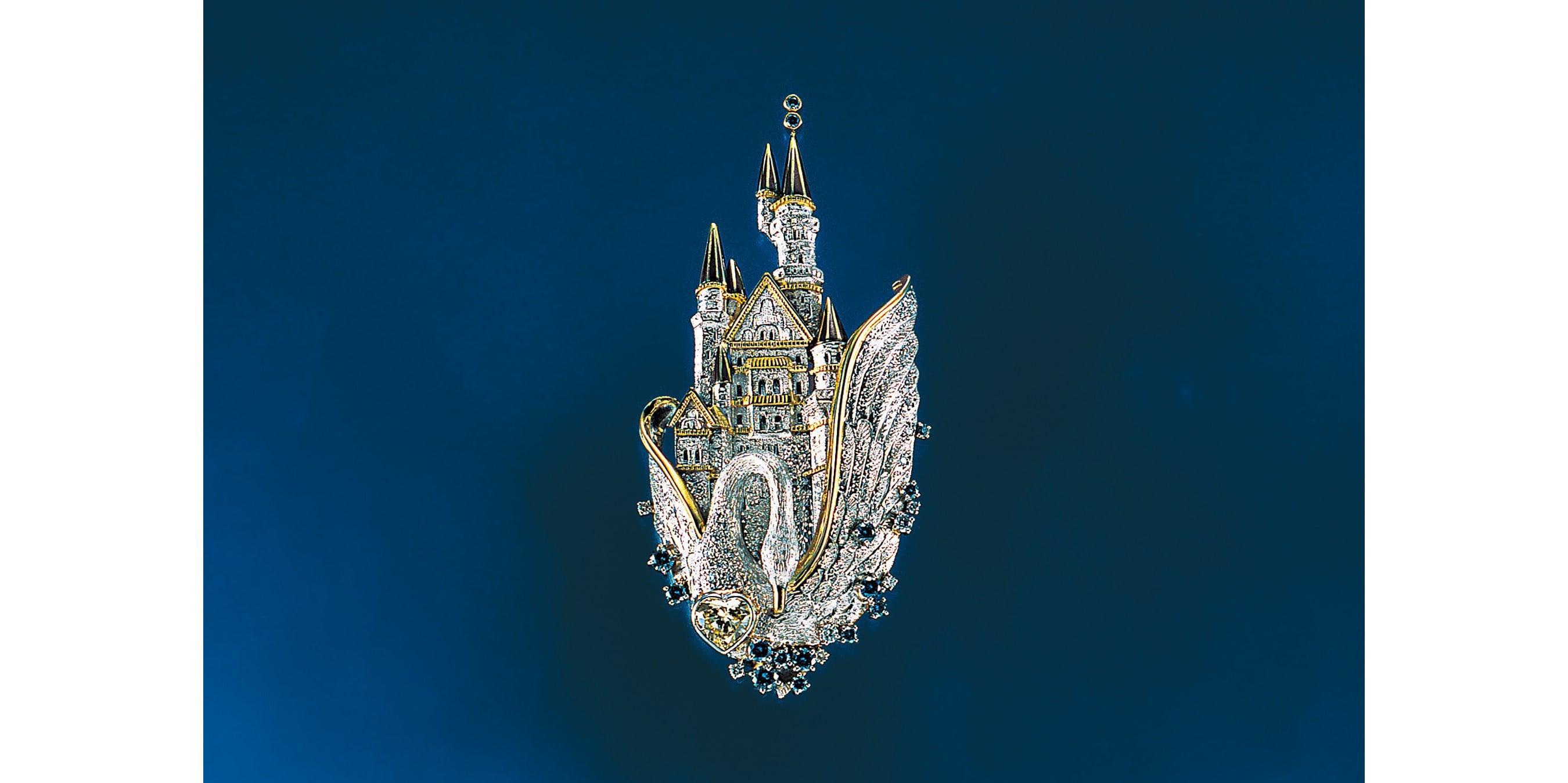 ドイツの古城、ノインシュバンシュタイン城と、羽を広げた白鳥を描写した壮大な作品。城の先端には赤銅を施し、全体にタガネで複雑なテクスチャーを加え、奥行き感のある仕上がりとなっている。 「ノイシュバンシュタイン城」ブローチ/ペンダント。K18イエローゴールド・Pt900・赤銅・ダイヤモンド。5,100,000円 税別(参考上代)