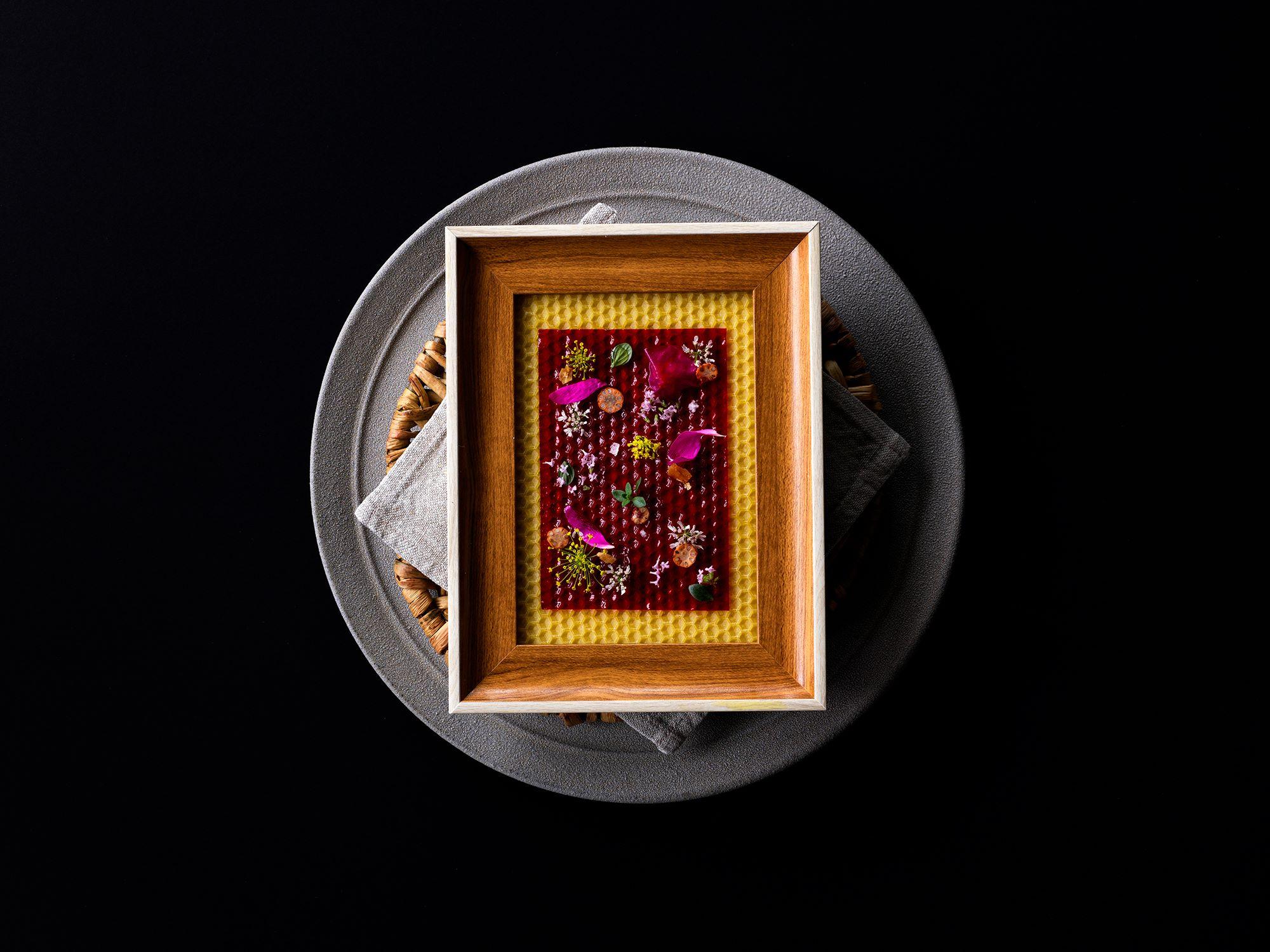 INUAの魅力を鮮明に表現する料理「プラムレザーとアロマティックフラワー」。プラムの果汁をシートにし、食べられる花やハーブなどをのせ、蜜蝋の上に置く。Photography Jason Loucas