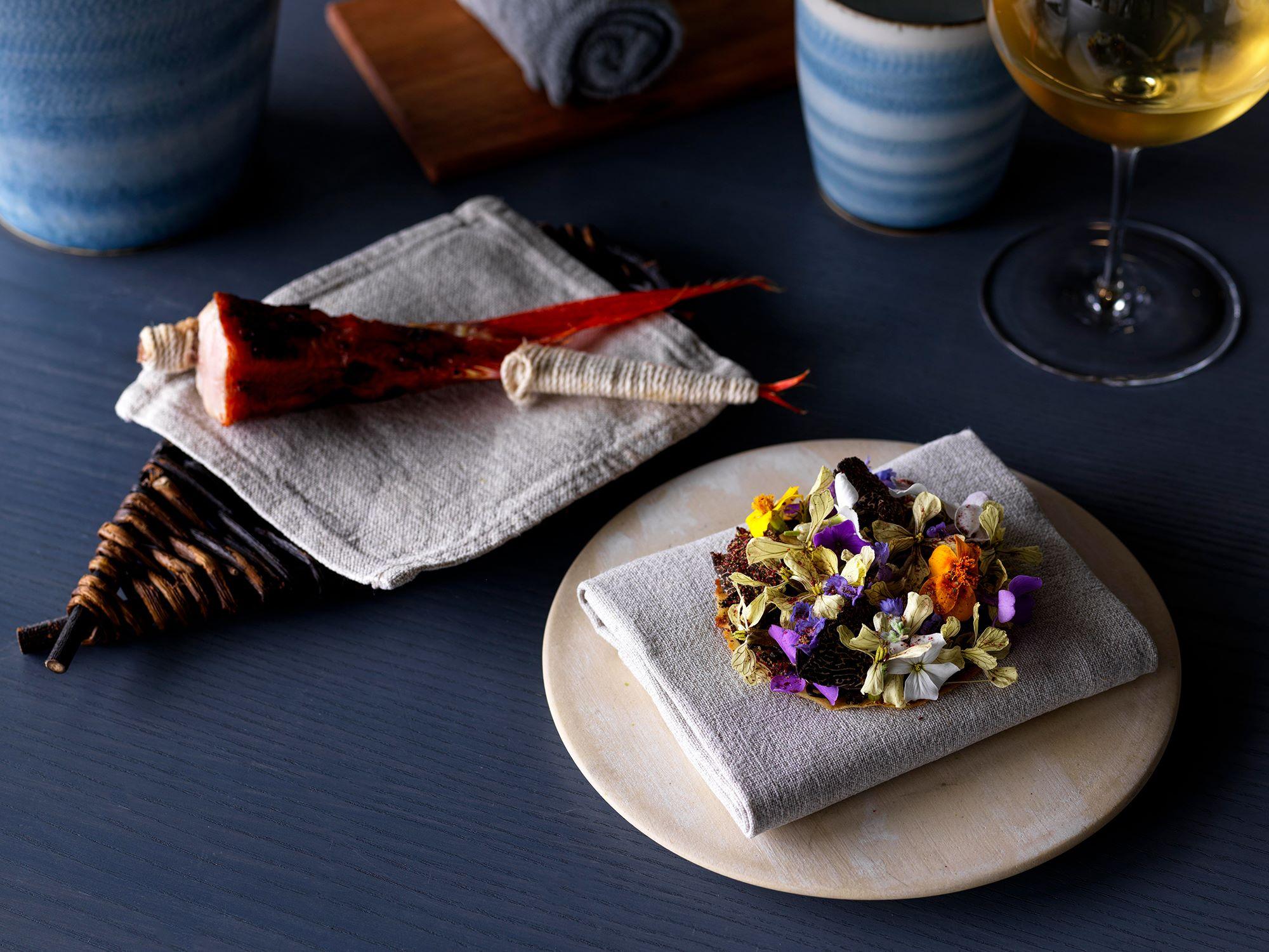 金目鯛にハバネロ味噌の風味をつけて炭火で焼いた料理。手で食べられるよう紐を巻いて。手前は黒トリュフをベースにしたピューレをのせた花のタルト。Photography Jason Loucas