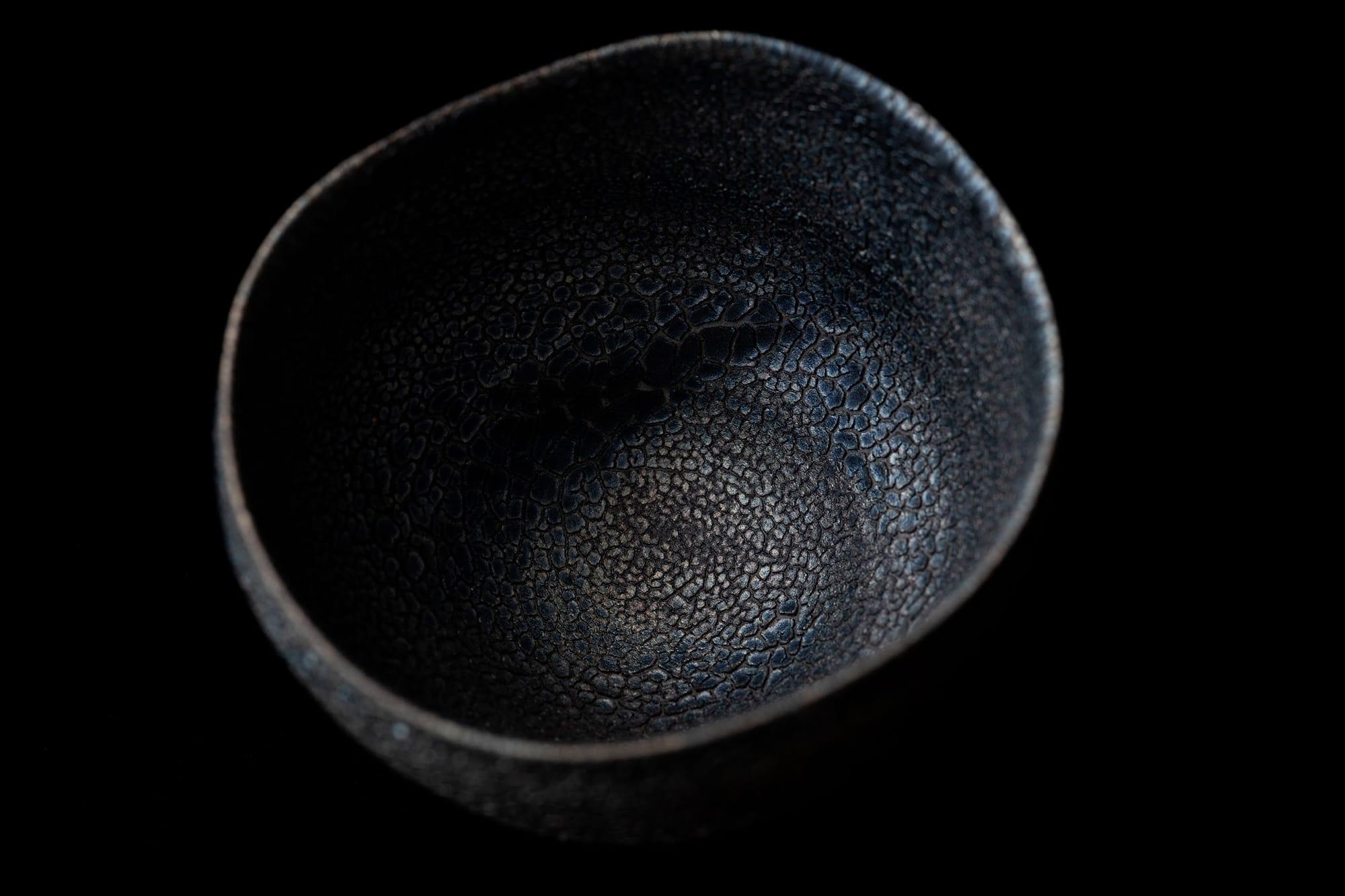 釉薬が蛇の鱗のようにひび割れ青黒く光る。大蔵寂土窯変碗。2019年制作 ギャラリー册にて展示。Photography by Ikeda Yuichi