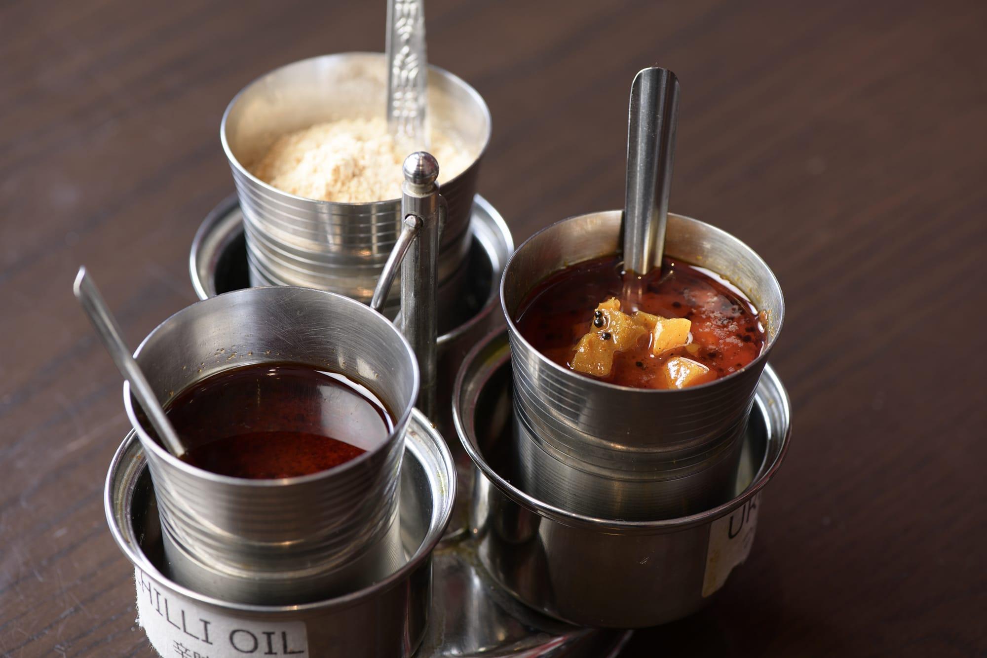 テーブルにはひよこ豆のふりかけ、大根の漬物と辛さの調整ができるチリオイルが置かれている。
