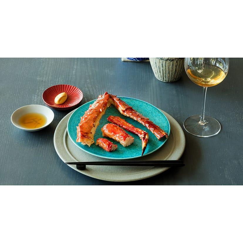 北海道産のタラバガニの炭火焼き。唐辛子を発酵させた新潟産の「かんずり」を用いたオイルを塗って焼く。サワガニでつくった魚醤で風味付けしたINUAのオリジナルポン酢、カニみそで作ったソースなどを添えて、箸で楽しむ。
