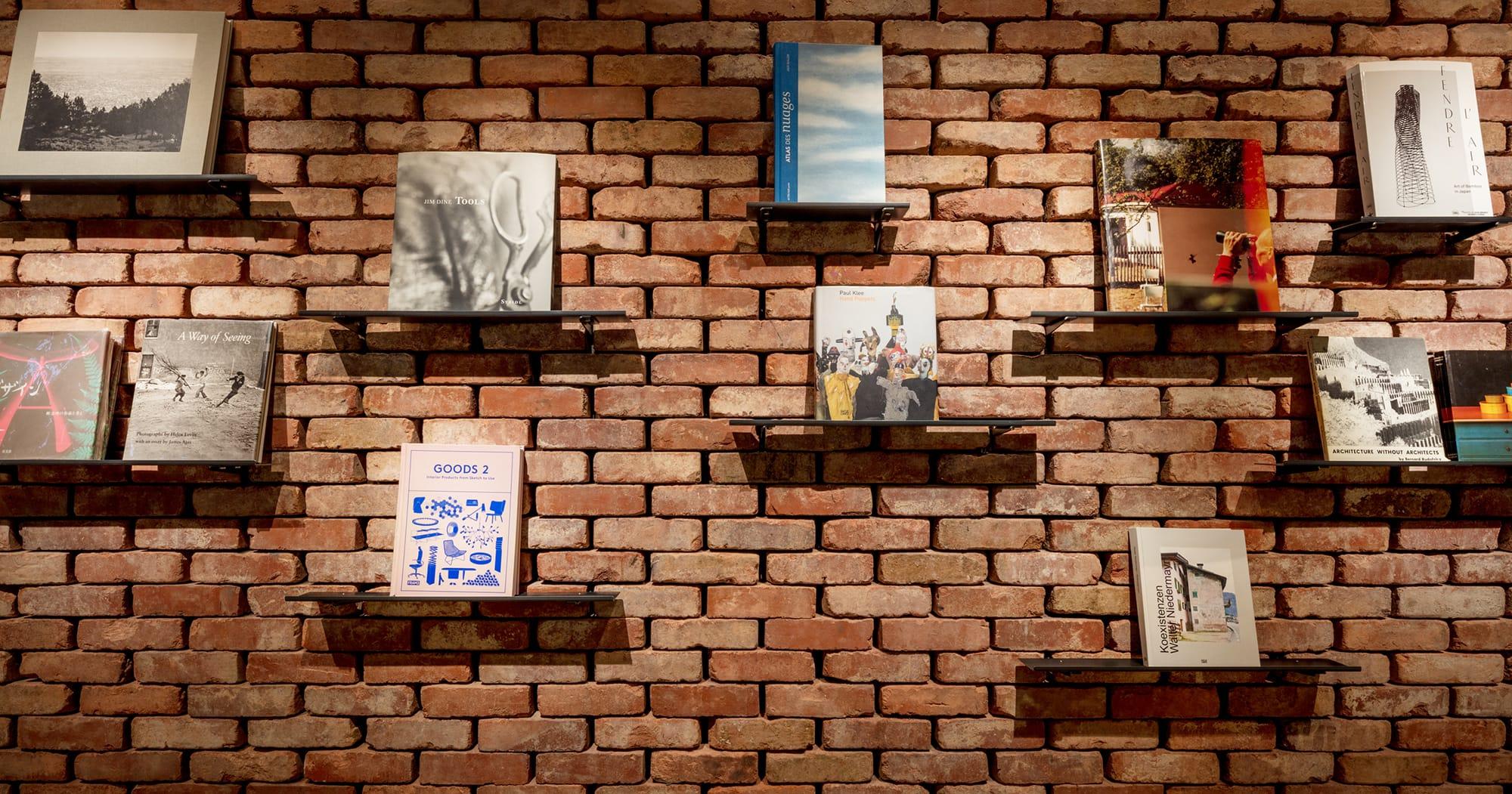 6階のATELIER MUJIのレンガの壁に飾られた希少な本。