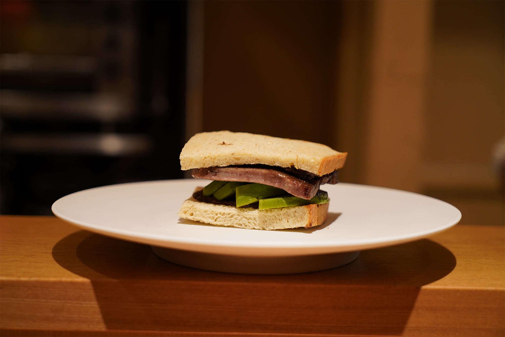 「アボカド 牛タン マカダミアナッツ」。レシピ提供者のカルドソに「徳吉のレシピがほしい」と言わしめた一品。薄切りトーストにスライスしたアボカドとマヨネーズを合わせただけのレシピから、分厚くカットしたジューシーな牛タンの歯ごたえとアボカドのクリーミーなテクスチャを対比するガストロノミーな一品へと変化させた。