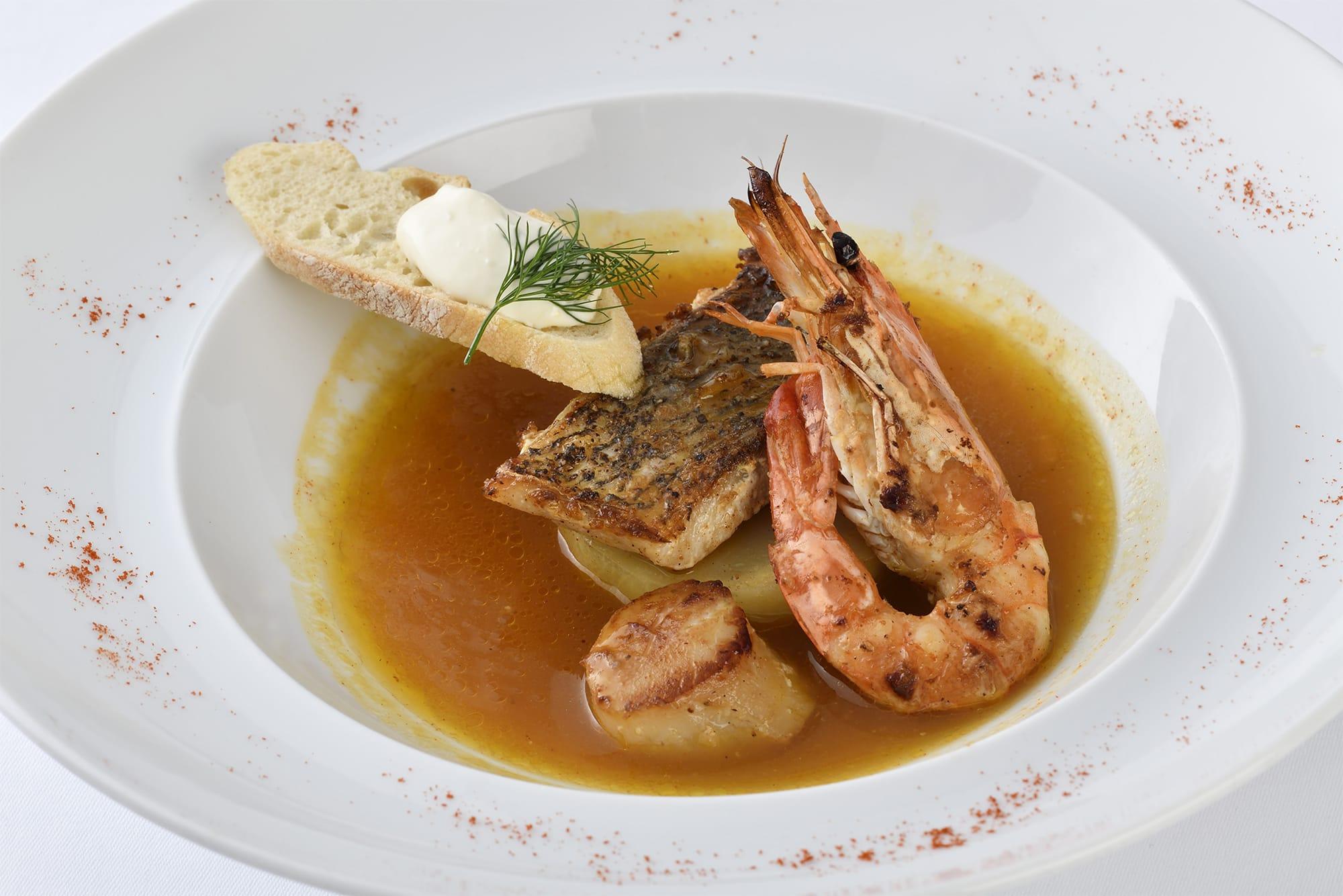 """魚料理はハンガリーの名物スープを取り入れた「魚介のロースト パプリカ風味のブイヤベース""""ハラースレー"""" にんにくの香るサワークリームと共に」。"""