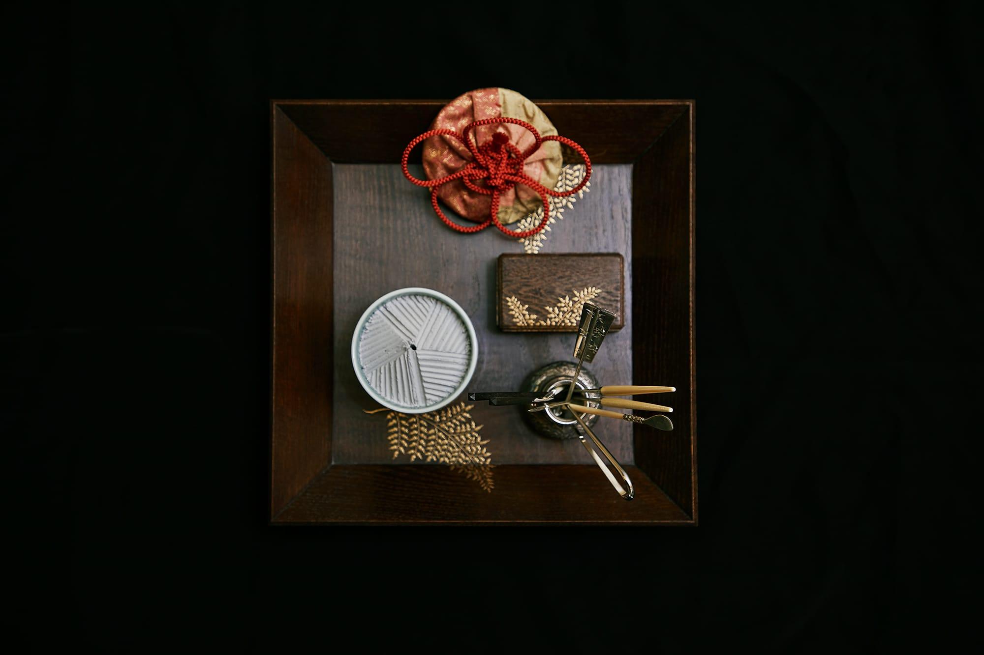盆の上の道具。奥から時計回りに、香木が入った志野袋、銀葉入れ、火箸や灰押さえなどの火道具、香炉。志野袋の緒は、季節の梅の花の形に結ばれている。