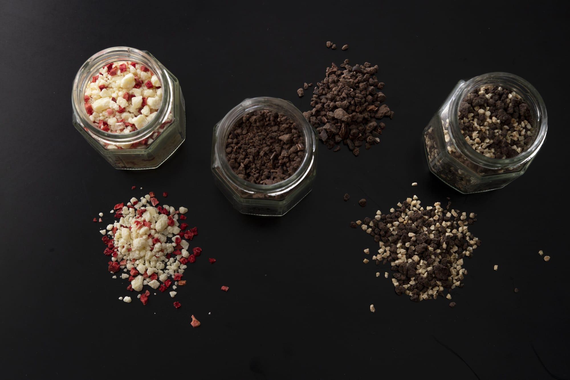 チョコレートの楽しみ方が広がる「フリカケ」。左から、フリーズドライベリーとホワイトチョコレートの「ホワイトベリー」(970円)、苦味とほのかな酸味「タンザニア」(800円)、アーモンド入りの「コロンビア」(800円)。ミルクに溶かしてホットチョコレートにもできる。(すべて税込)
