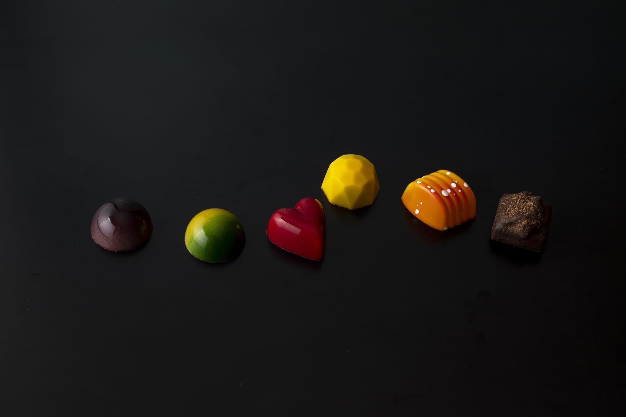 ベルギーのチョコレートは、モールド(型)を使ったものが主流。中にはフレッシュ感のあるガナッシュが詰められている。左から、ブルーベリー&カシスの「ヴィオレ」、「ライムジンジャー」、「フランボワーズ」、「パッション」、「オレンジ」、ベルギーを代表するスパイスクッキーを入れた「スペキュロス・プリュノー」。各223円(税別)
