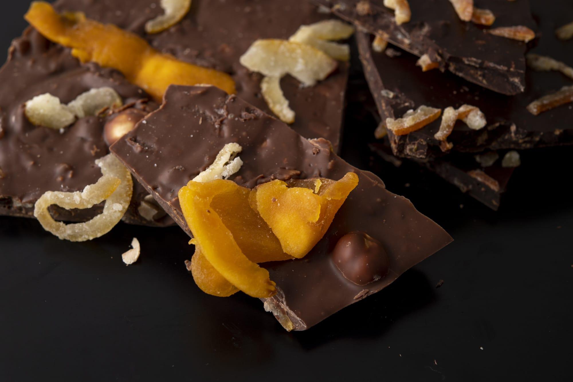 ベルギーでよく見られる、ナッツやドライフルーツが入った量り売りの板チョコ。ミルクチョコレートはドライマンゴー、マカダミアナッツ、クルミ、アーモンド、レモンピール入り。ほろ苦いブラッドオレンジピールとアーモンドの入ったダークチョコレートは、ロイヤルティーヌも入ってサクサク食感「プラック・ショコラ」800円/100g(税別)
