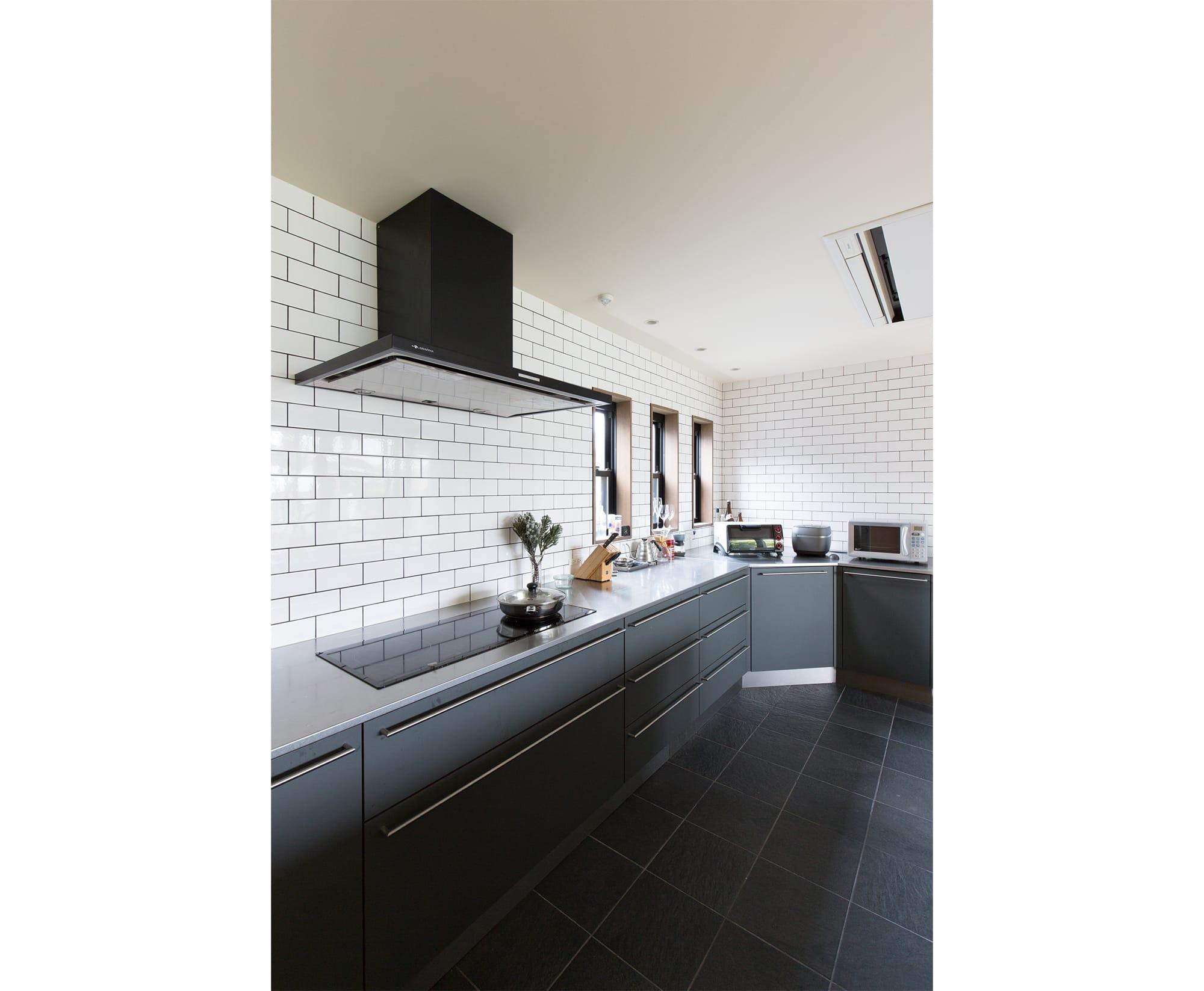 ダイニングスペースは木の温もりを大切にし、キッチンスペースはモノトーンですっきりとデザイン。 キッチン製作=インターテック /住宅=長縄貴人 Photography by Yoshiro Imai