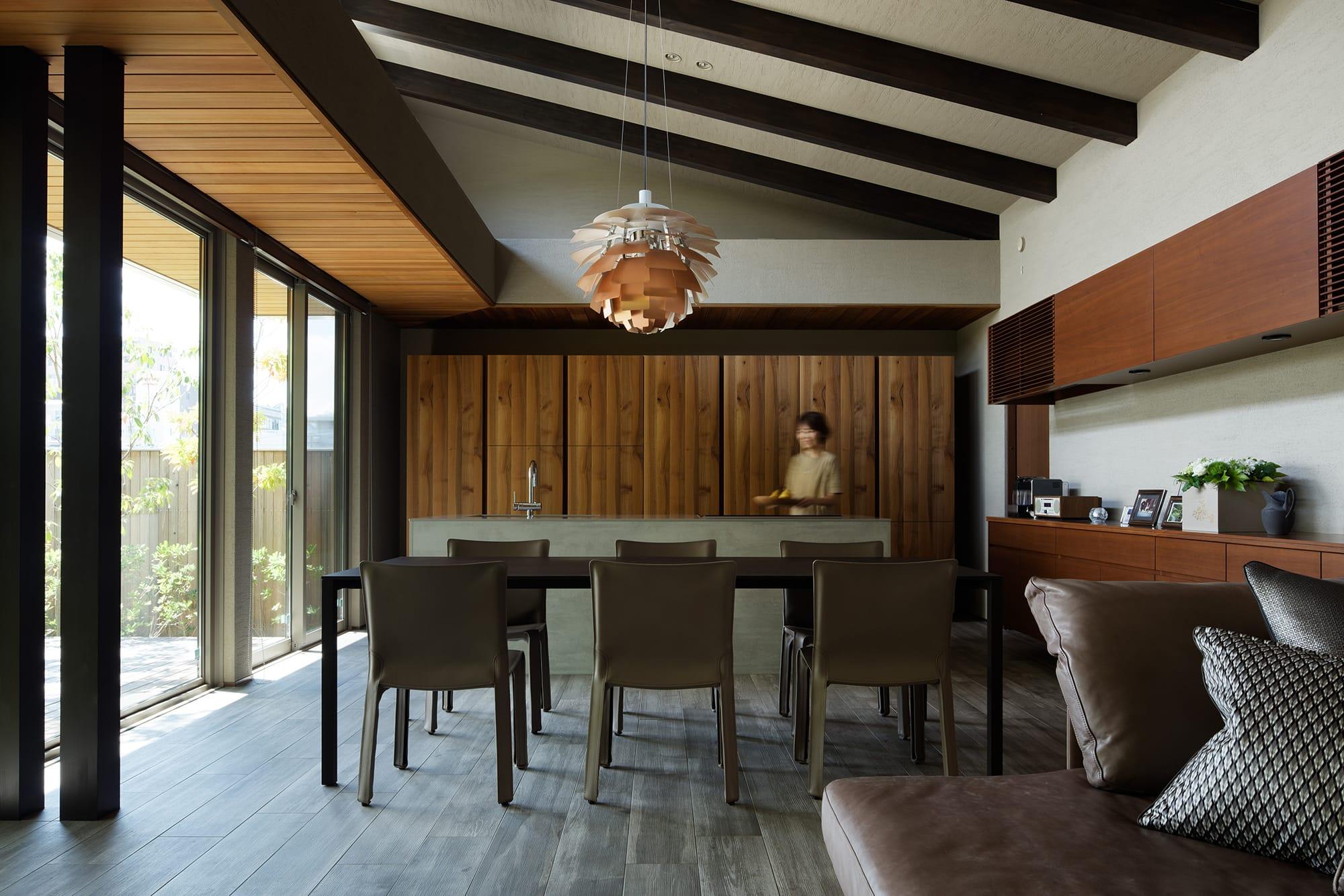 壁面キャビネットのウォルナット材に合わせてテーブルとチェアをセレクト。天板が薄い線の細いカッシーナの「ナーン」のテーブルがキッチンの直線のデザインを邪魔しない。 キッチン製作=ユーロモビル大阪/住宅=積水ハウス Photography by Ken Shirotani