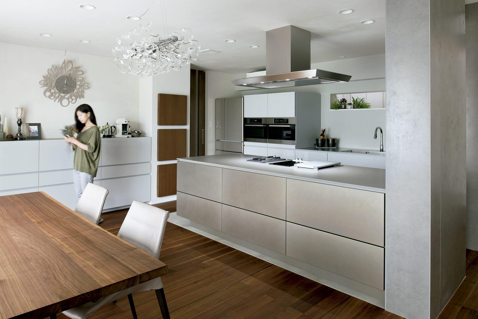 シルバーブラウンカラーに加工したアルミ材を使用したキッチン。光によって変化する色や風合いを楽しめる空間だ。キッチン製作=アムスタイル/住宅設計=青島裕之 Photography by Yukinori Okamura