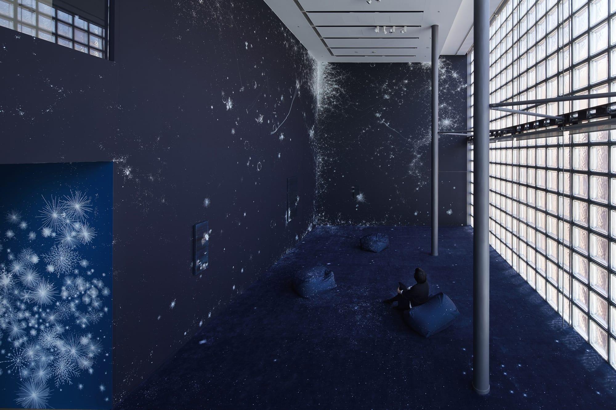 濃紺の壁面に無数の星のモチーフが描き出され、崇高な宇宙空間が表現されている。  展示風景/ Installation viewコズミック・ガーデン| 2020 |マーカー、アクリル、ペンキ、カンヴァス、木パネル、カーペット、スピーカー Cosmic Garden | 2020 | Permanent pen, acrylic, paint, wood panel, carpet, speaker ©Nacása & Partners Inc. / Courtesy of Fondation d'entreprise Hermès