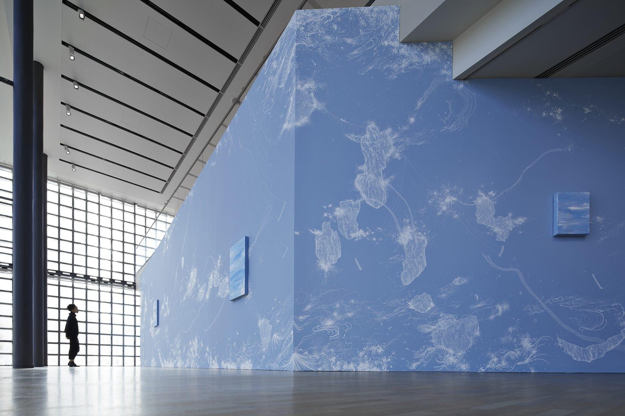 壁一面に広がる宇宙を象徴的に表すブルーをベースとして、繊細なラインで波などのモチーフが描き出されている。  展示風景/ Installation viewコズミック・ガーデン| 2020 | マーカー、アクリル、ペンキ、カンヴァス、木パネル、カーペット、スピーカー Cosmic Garden | 2020 | Permanent pen, acrylic, paint, wood panel, carpet, speaker ©Nacása & Partners Inc. / Courtesy of Fondation d'entreprise Hermès