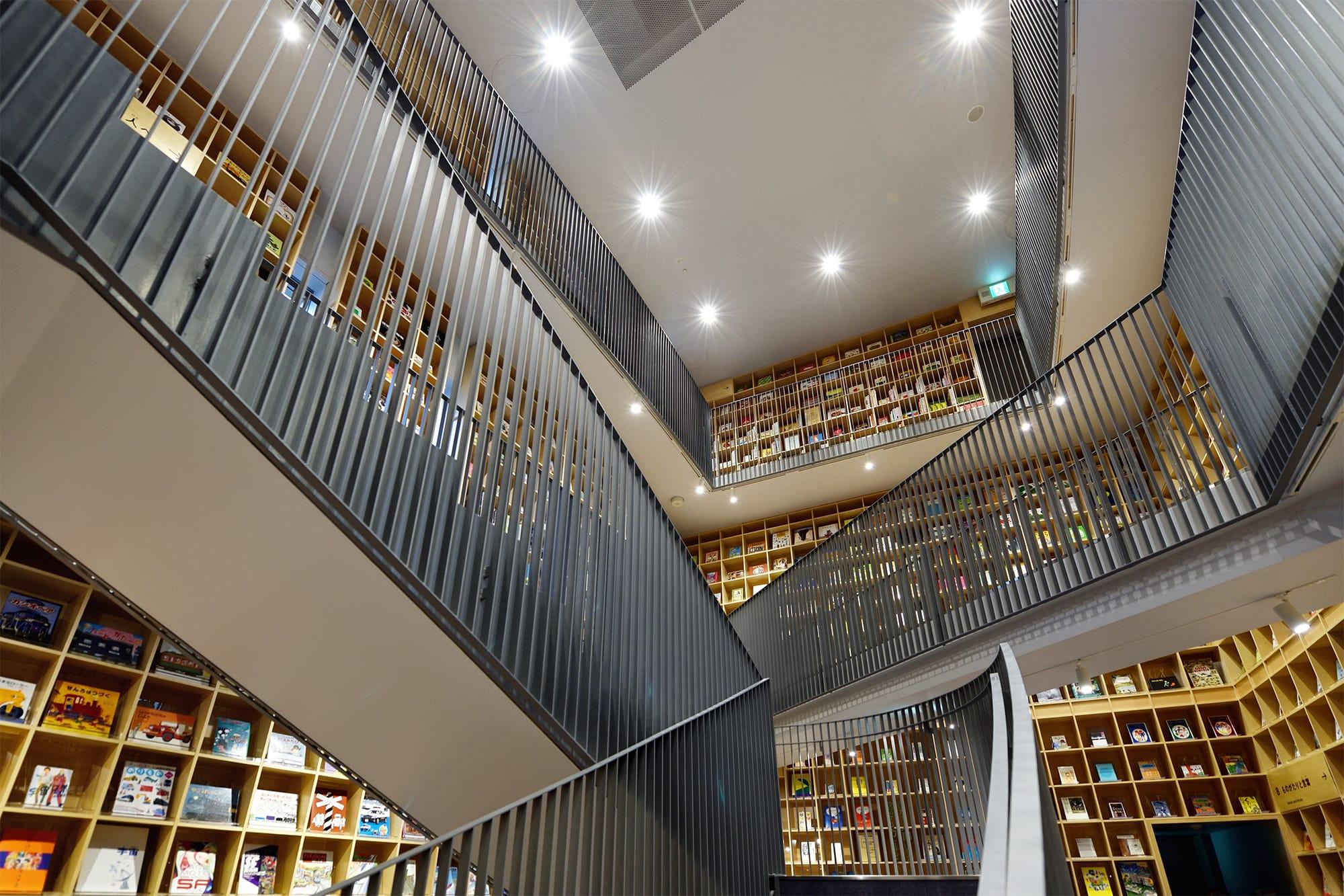 3階分の吹き抜けから、天井まで届く書架を望む。隙間から川や緑が垣間見え、圧迫感どころか安らぎさえ覚える設計だ。