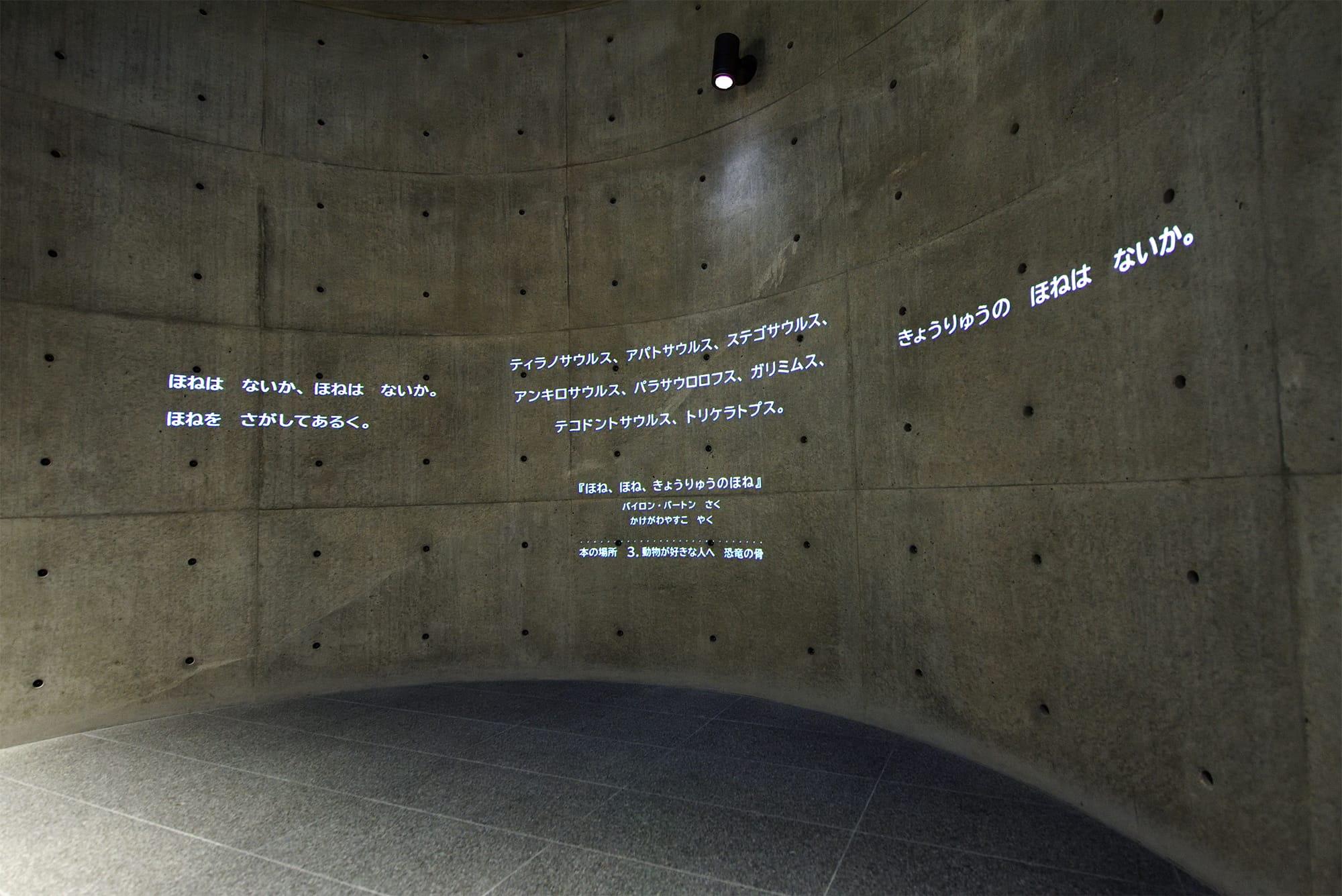 薄暗い円筒に天井から差し込む光、ときおり壁に現れる本の一節。1階の奥に広がる何もない空間は、物語の世界への扉だ。