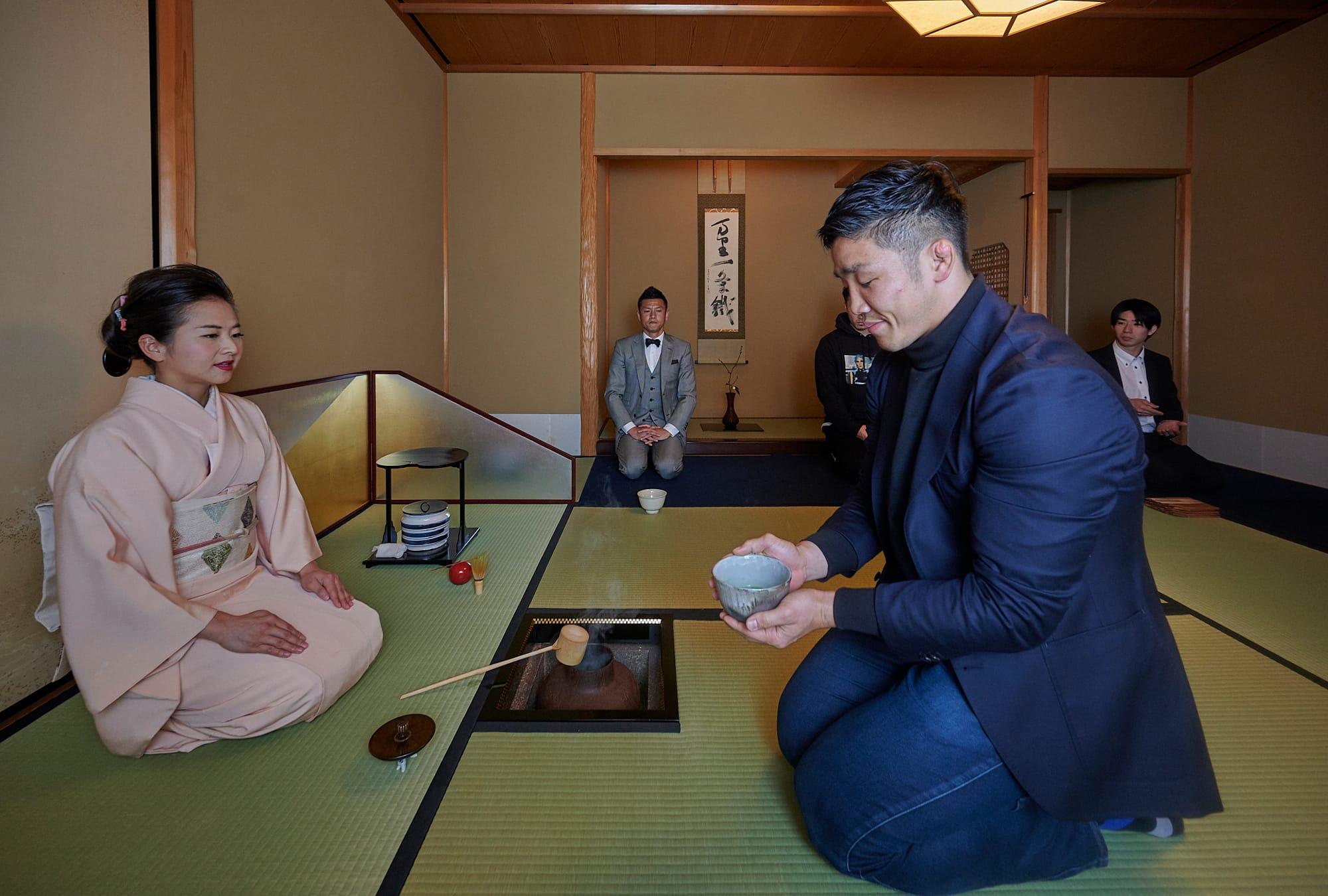 金正奎接過主人小堀宗翔的茶碗。在自家中也品茶的他,慎重的動作。金正奎是橄欖球「NTT Communications Shining Arcs」隊長,位置是側衛。