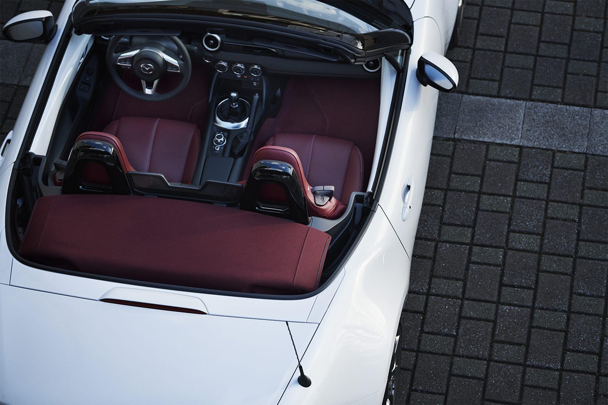 「100周年特別記念車 ロードスター」のみ、ソフトトップにダークチェリーカラーを採用。スノーフレイクホワイトパールマイカのエクステリアカラーとの対比も美しい。