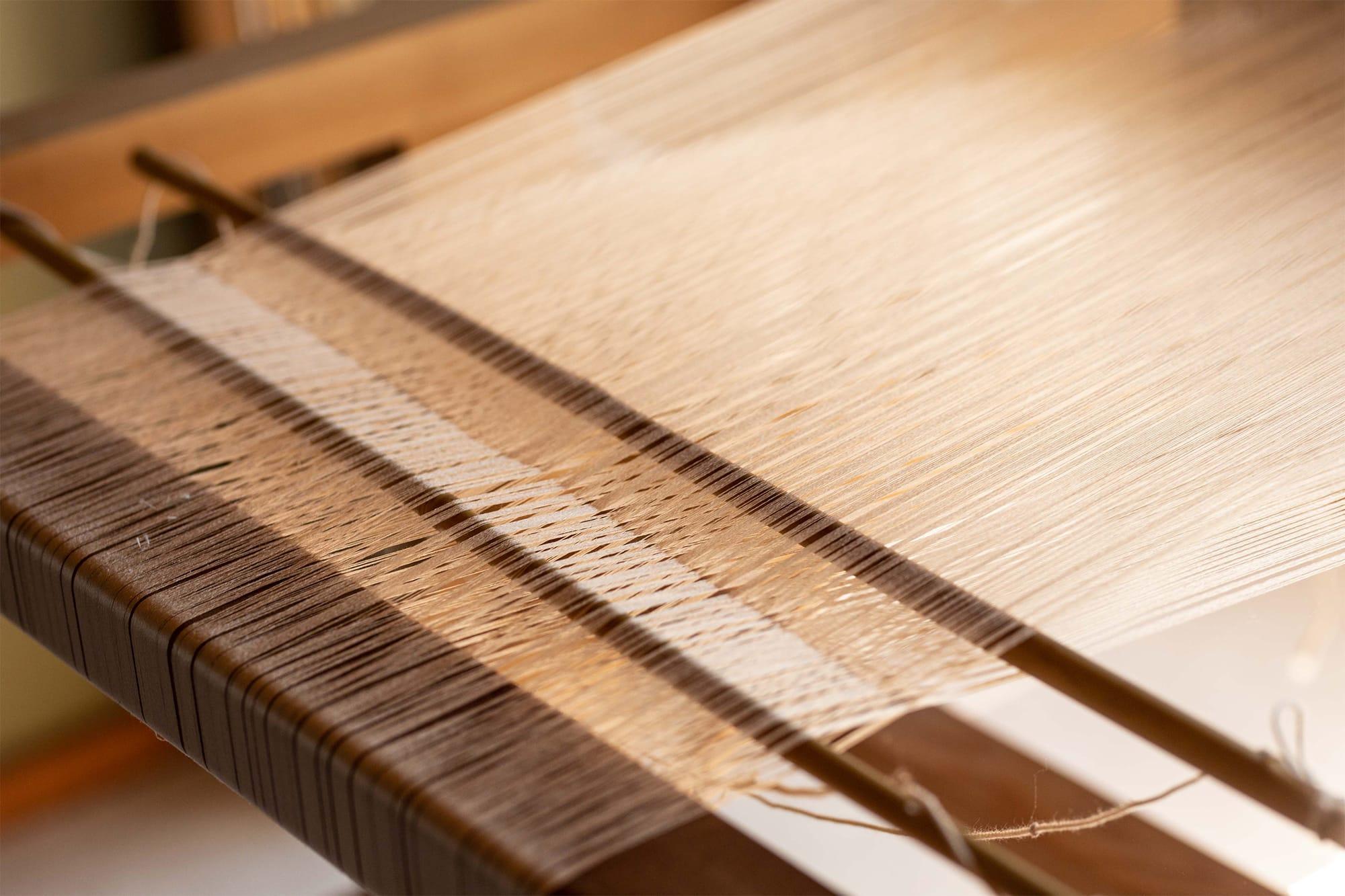 美しく染められた生糸は丁寧に手織りをしていく。