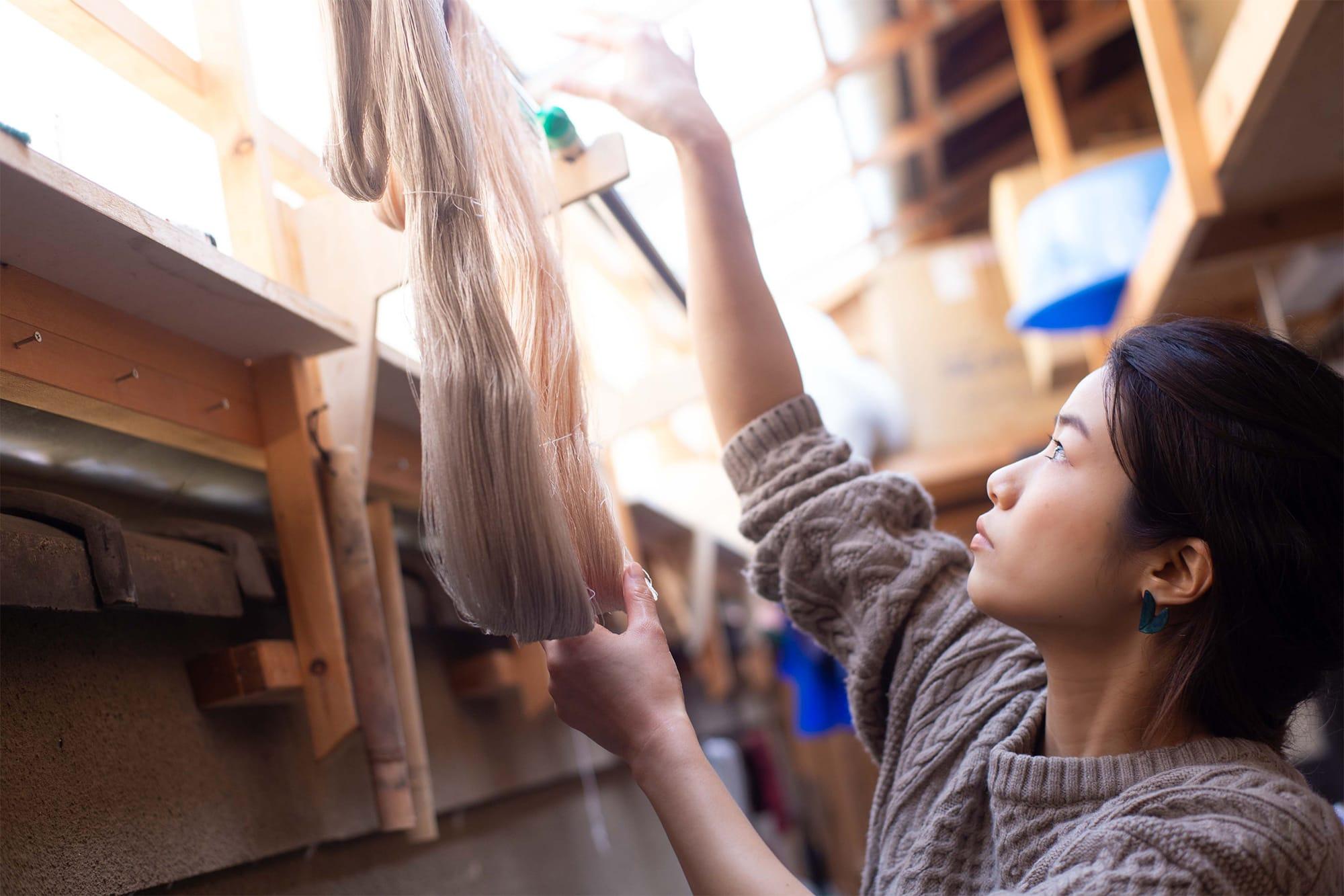 アトリエシムラで生み出されるきものやストールなどは、すべて手機による手織。草木の色で染めた紬糸を、経糸・緯糸それぞれ丹念に織りあげていく。