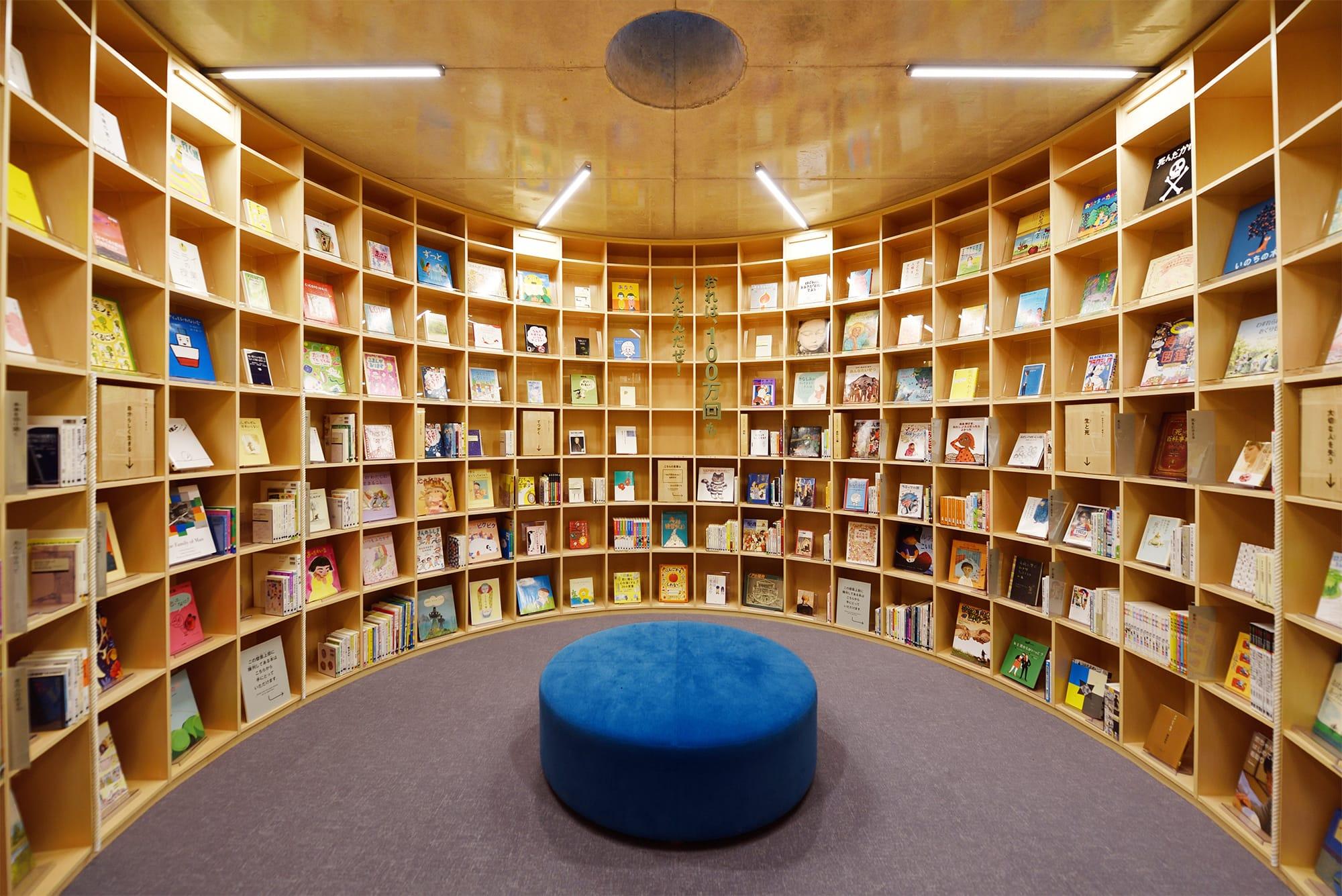 横穴から潜り込むようにして入る円形の書架は、輪廻をイメージした配架に。1人静かに心を落ち着けて読書が楽しむこともできる。