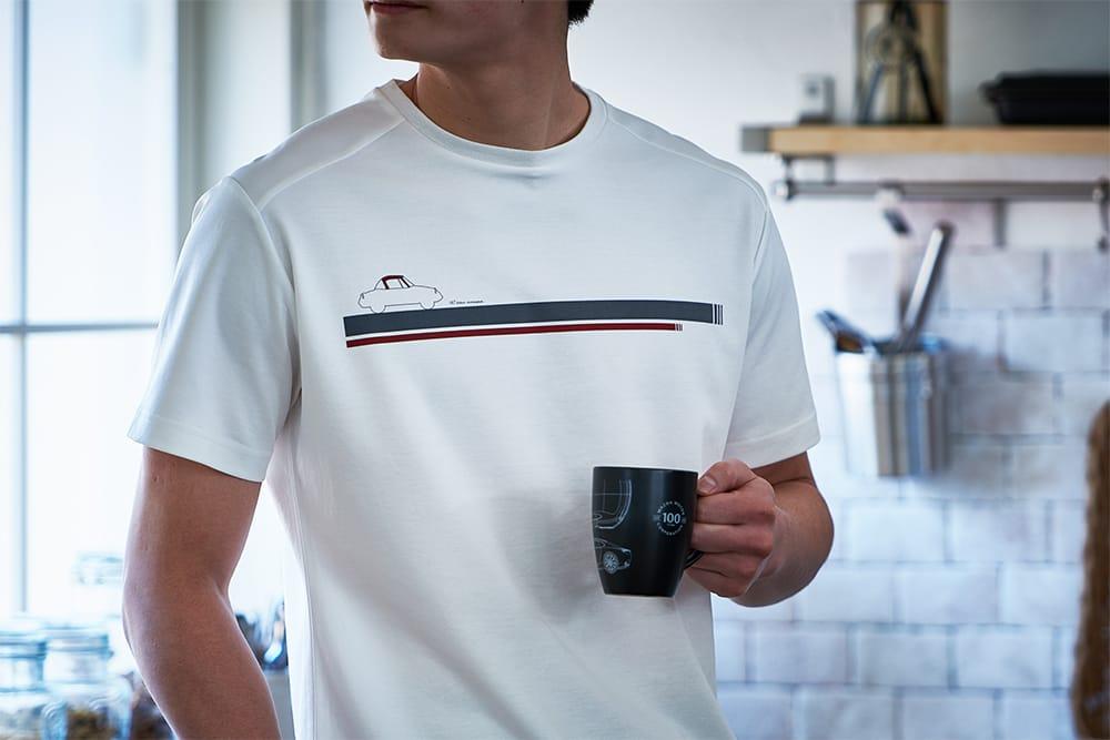 マツダデザイン本部監修のもとに企画・開発された「100THコレクション Tシャツ」6,820円や、「マグカップ」2,200円。その他、タオル2,200円、ポストカード1,100円など、ユニークなアイテムが揃っている。(すべて税込)