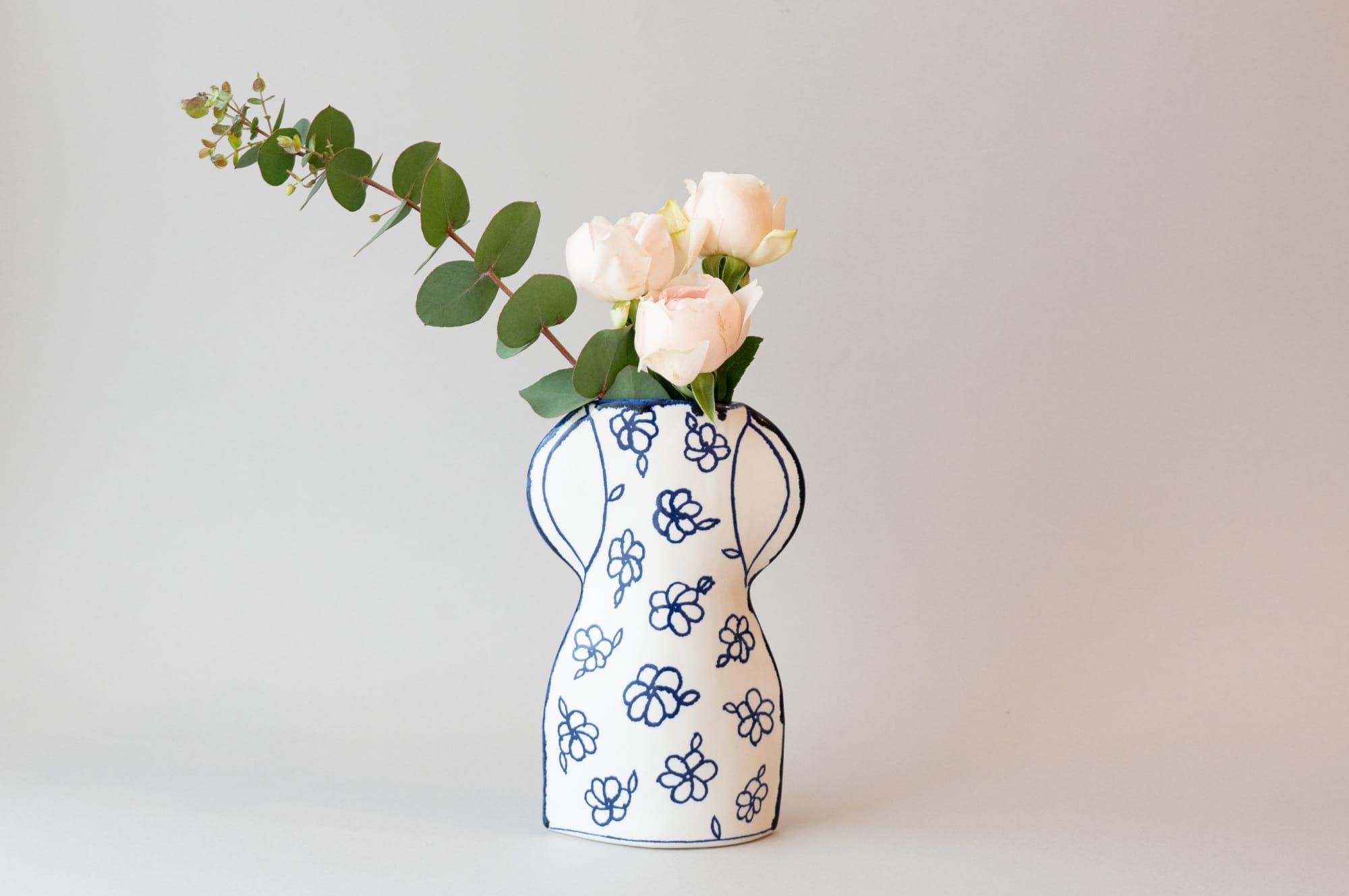 お花屋さんで育ったマリアンヌのトレードマークとも言える花柄を描いた作品「花柄のかびん」。白地にマリアンヌブルーが映える。