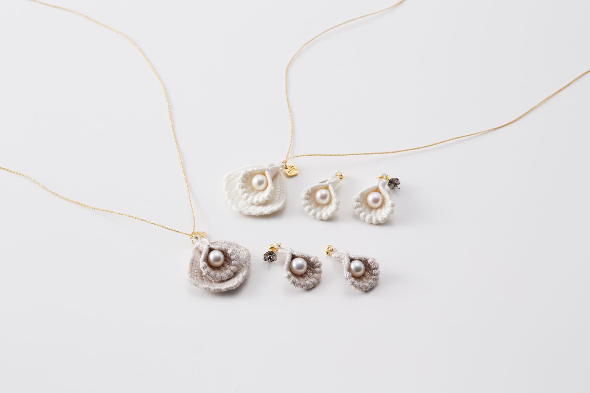 貝殻はシルク糸の刺繍、中心に本物のアコヤ貝を配置。色は上がホワイト、下がグレージュの2種類。ブランドロゴのチャームもアクセントに。