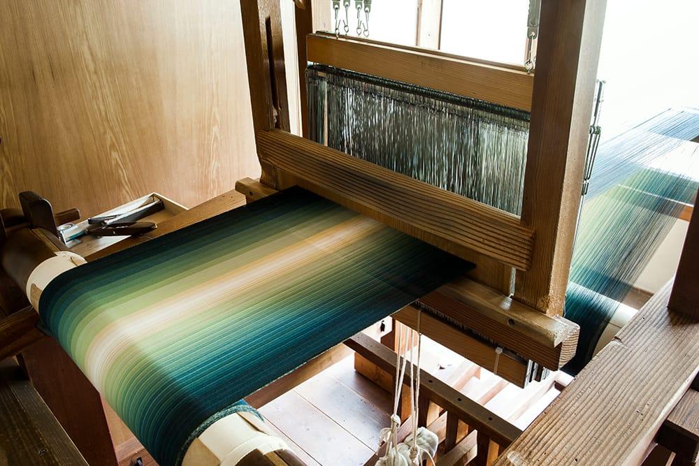 縞は経(たて)糸の並びで柄が決まる。たて縞が特徴の「小倉織」にとって重要な過程。