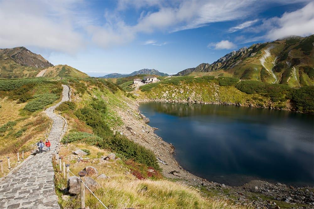周囲630mの火山湖、みくりが池。池の奥の白い建物は、日本一高所(標高2,410m)にある天然温泉、みくりが池温泉。地獄谷を源泉とする白濁湯100%かけ流し。写真右端は立山三山(立山、浄土山、別山)の一峰、別山(べっさん/標高2,880m)。その左側の岩峰が剱岳。