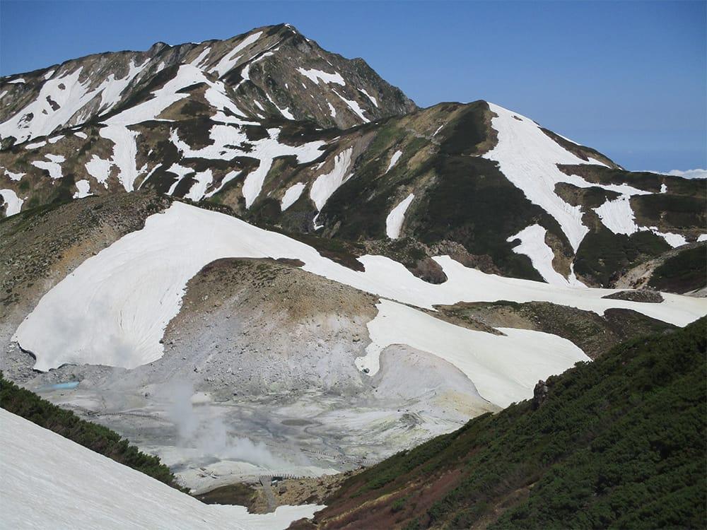 大日岳をバックに、エンマ台から眺める地獄谷。硫黄臭が立ち込め、有毒な火山ガスを発する場合もあるので、室堂ターミナル等にて注意情報を要チェック。エンマ台からさらに奥に位置する雷鳥荘付近からは、地獄谷の全容も見渡せる。