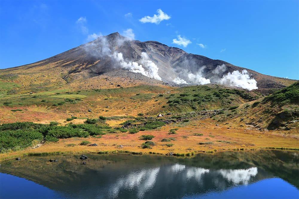 大雪山(だいせつざん/標高2,291m:旭岳 日本百名山)とは、北海道最高峰の旭岳(写真)を主峰とする火山群の総称。野趣あふれる神々しい景観からか、アイヌ語では畏敬の念をもって「カムイミンタラ(神々の遊ぶ庭)」と呼ばれている。ロープウェイ姿見駅から姿見池(写真)まで、約1.7kmの周回散策路がある。DATA 大雪山 旭岳ロープウェイ(北海道川上郡東川町旭岳温泉/0166-68-9111) 山麓駅~姿見駅 往復 大人3,200円(6/1~10/20)