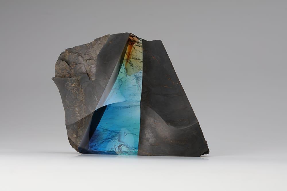 岩坂卓のオブジェ「Symbiosis #17」。自然がつくる形と人がつくる形が、互いを生かしつつ新たな形で共生することを石とガラスで表現。Photography by Suguru Iwasaka