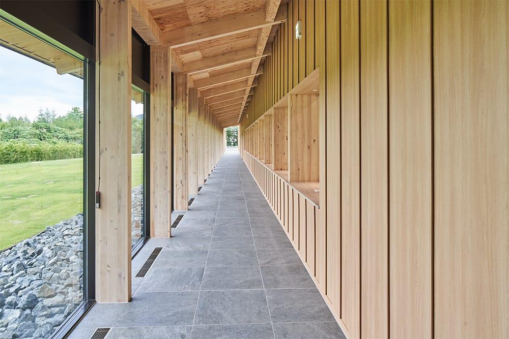写真右手側の組立工房は内廊下から見学できる。工房内からは豊かな緑と岩手山が見える。