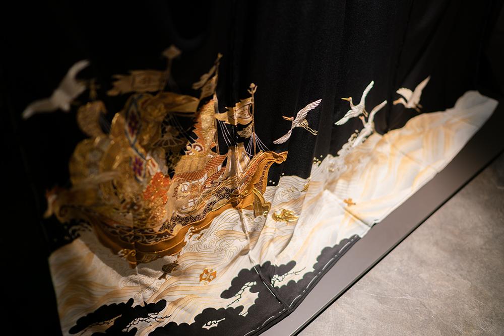 """一生同じつがいで添い遂げる鶴、永遠に絶えることのない波、そして七福神が乗る宝船など吉祥柄がすべて入れられた刺繍の黒留袖""""宝寿満帆""""。4,800,000円(税別)"""