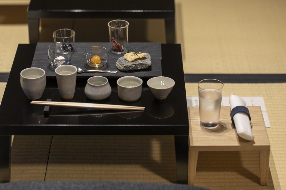 「長谷川栄雅 六本木」の日本酒体験の様子。脚付き膳に供される「長谷川栄雅」の日本酒5種類と小林シェフ創作のアテが並ぶ。