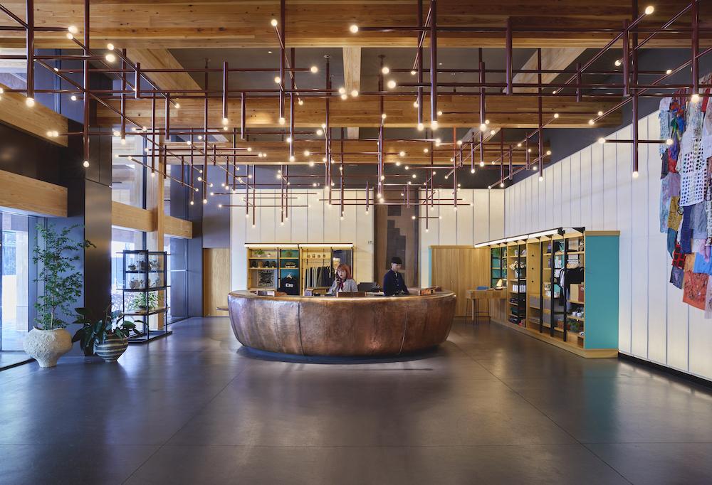 円形のフロントデスクがゲストを迎えるロビー。天井は隈研吾建築らしい木組みだ。布のタペストリーなど、ユニークなアートワークが楽しい。