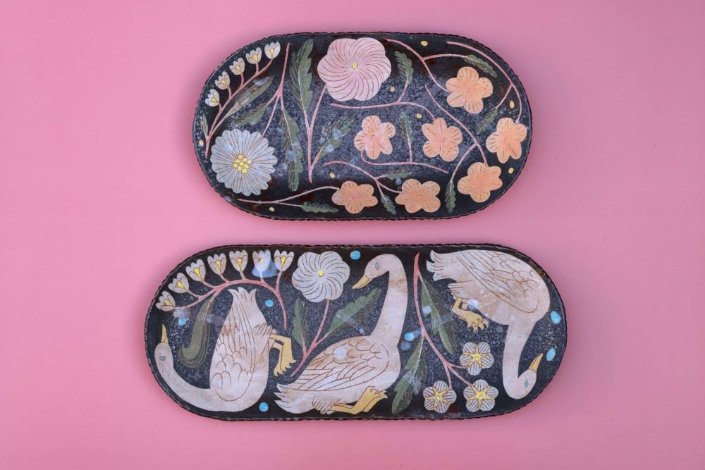 花々や動物たちが素朴なタッチで活き活きと描かれた器たち。全体に配置されたモチーフと独特の配色が黒地に浮かび上がる。