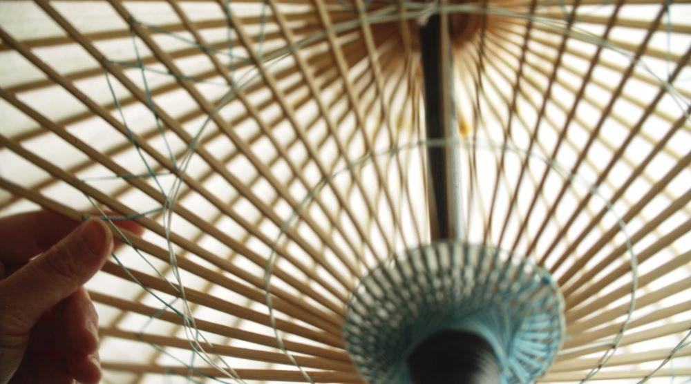 京都で唯一の和傘製造元、日吉屋による傘の制作の様子。竹の骨を手作業で組み、和紙を張り、油を紙に塗るといった工程を経て完成する。