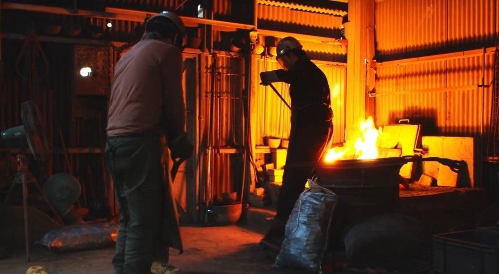 工房内の炉から、溶けた合金を取り出す作業の様子。